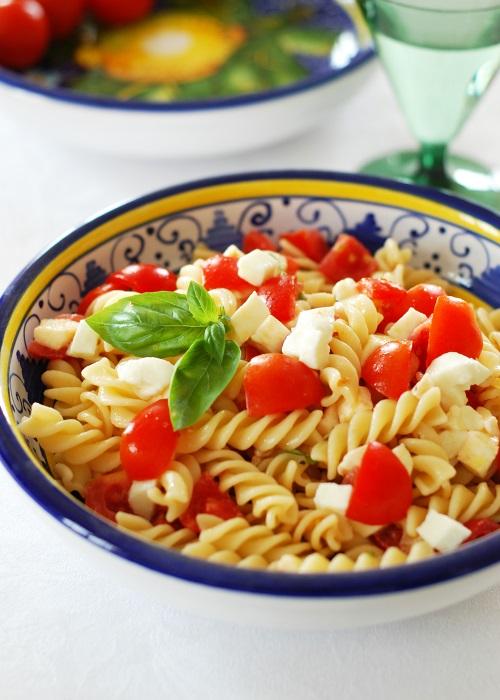 Insalata fredda di pasta con pomodorini, mozzarella e olio al basilico